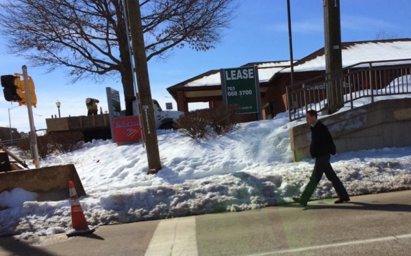 A pedestrian avoids the snow by walking near traffic at Sunset Hills and Wiehle Avenue/Credit: Bruce Wright