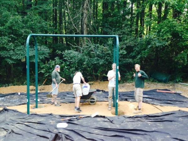 Reston Association worker install new  swings in meadow area near Lake Thoreau