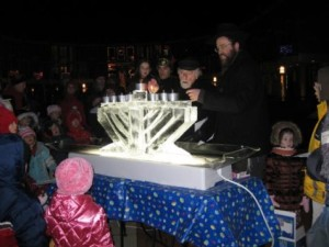 Reston founder Bob Simon lights the Menorah at previous Lake Anne Chanukah celebration/Photo courtesy of Chabad Reston-Herndon