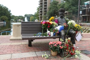 Flowers and candle at statue of Bob Simon at Lake Anne