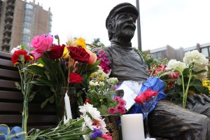 Flowers, candles and a martini glass at the statue of Bob Simon
