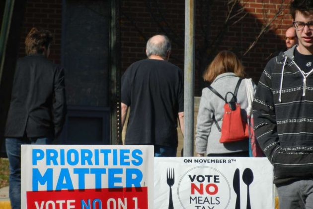 Voters pass by rows of campaign signs at the South Lakes High School polling place on Election Day 2016.
