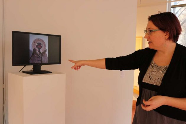 Erica Harrison, GRACE associate curator, shows a piece by Maelle Doliveux