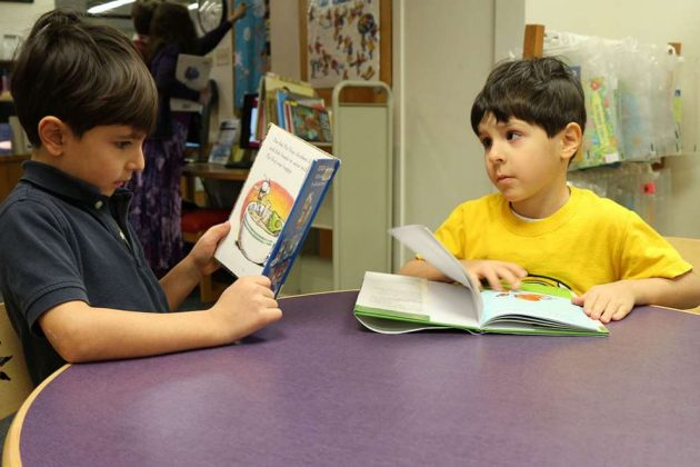 Brothers Owais, left, and Yunis Oumera, of Herndon, read at the Reston Regional Library.