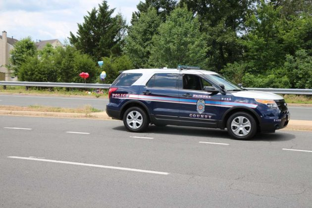 A Fairfax County police vehicle oversees a memorial for slain Reston teen Nabra Hassanen.